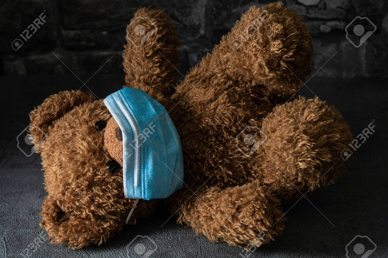 Teddy bear with surgical mask in dramatic light, concept of the novel coronavirus and its impact on children.Teddy bear with surgical mask in dramatic light, concept of the novel coronavirus and its impact on children. - 149442393