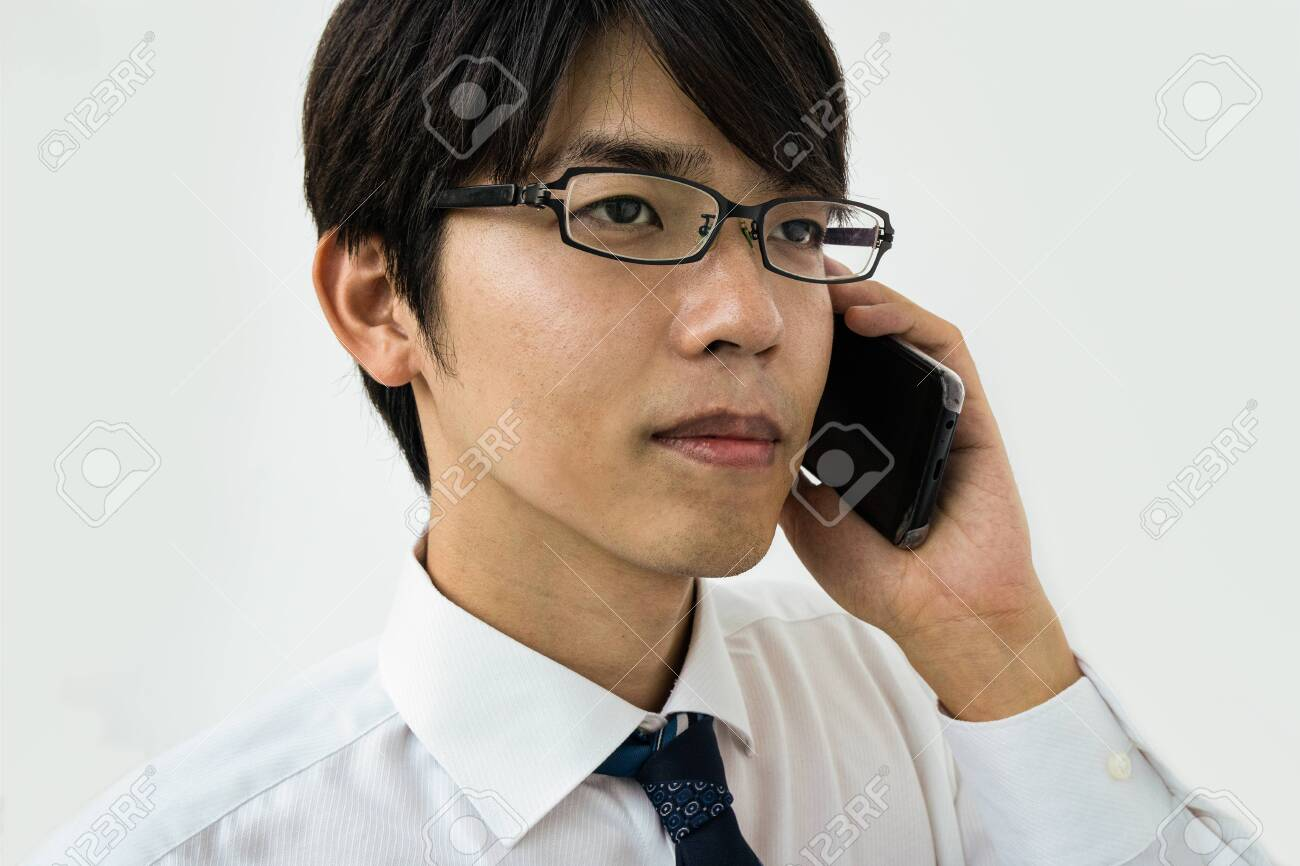 Young Japanese businessman talking on the phone. Isolated on white. - 149445800