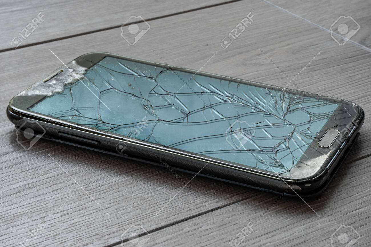 Broken smartphone on the floor. The screen is cracked and the phone is damaged. - 149445872