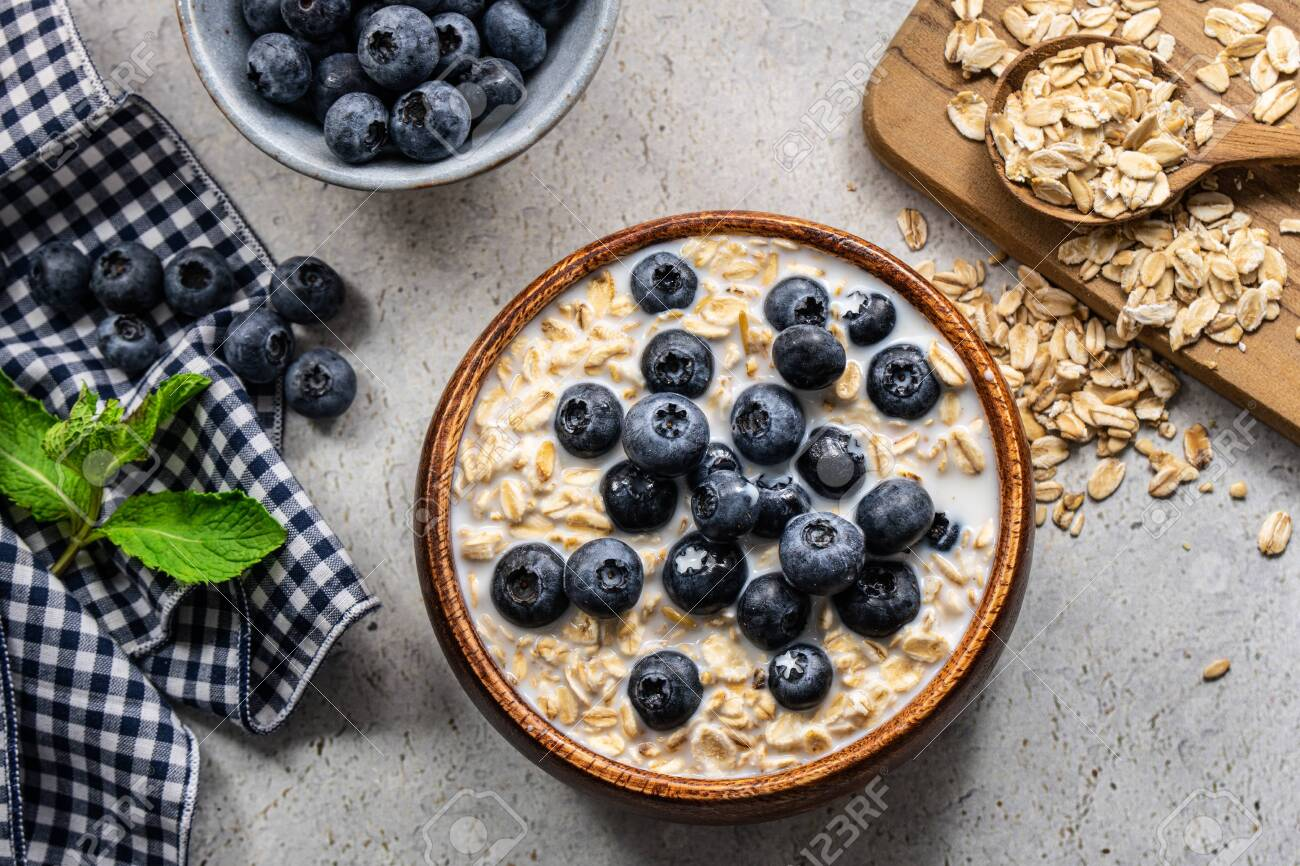 Healthy granola breakfast consisting of cereal, blueberries, banana and honey. - 149232049