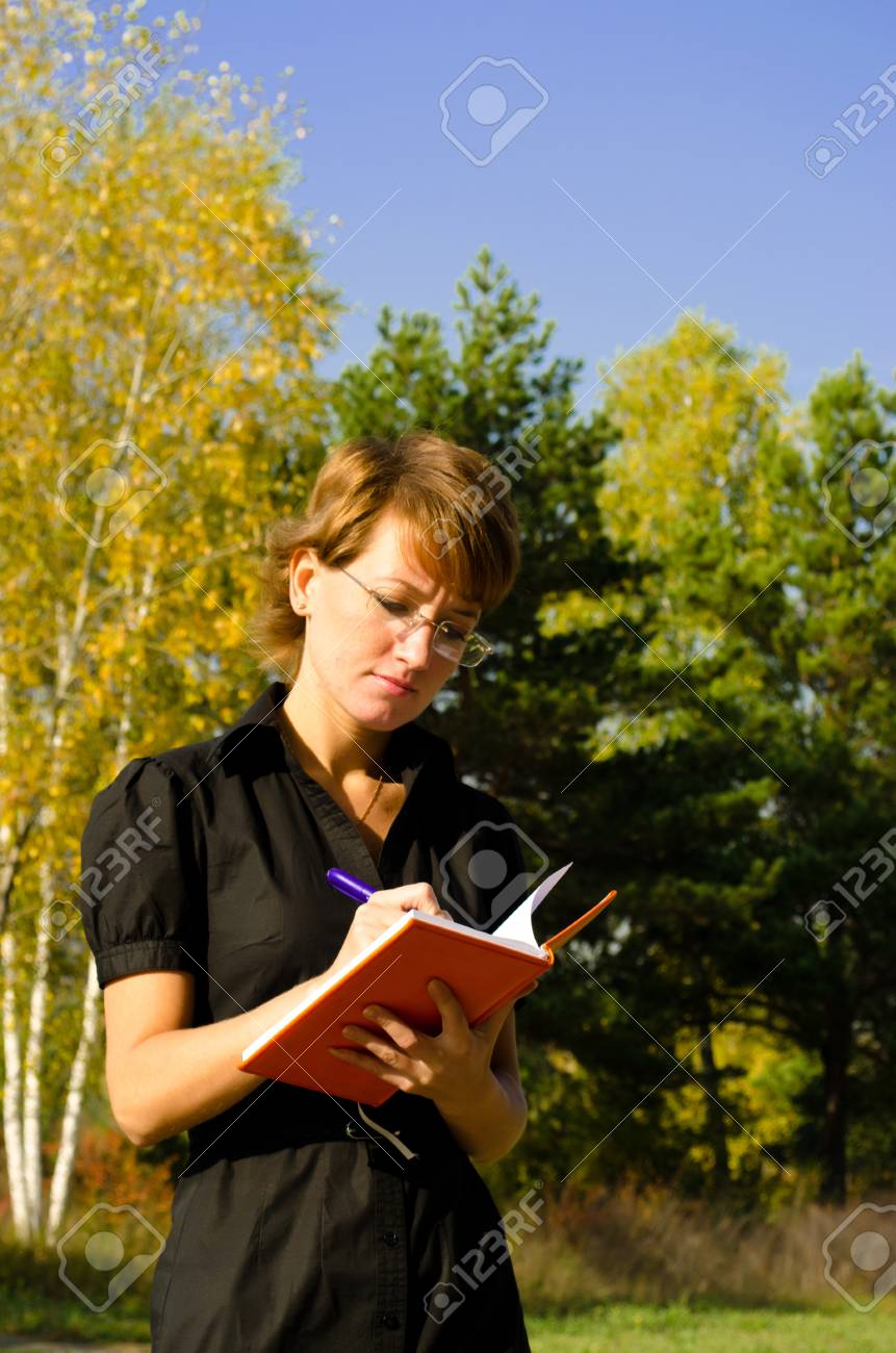 Businesswoman writing in a notebook Stock Photo - 15891628