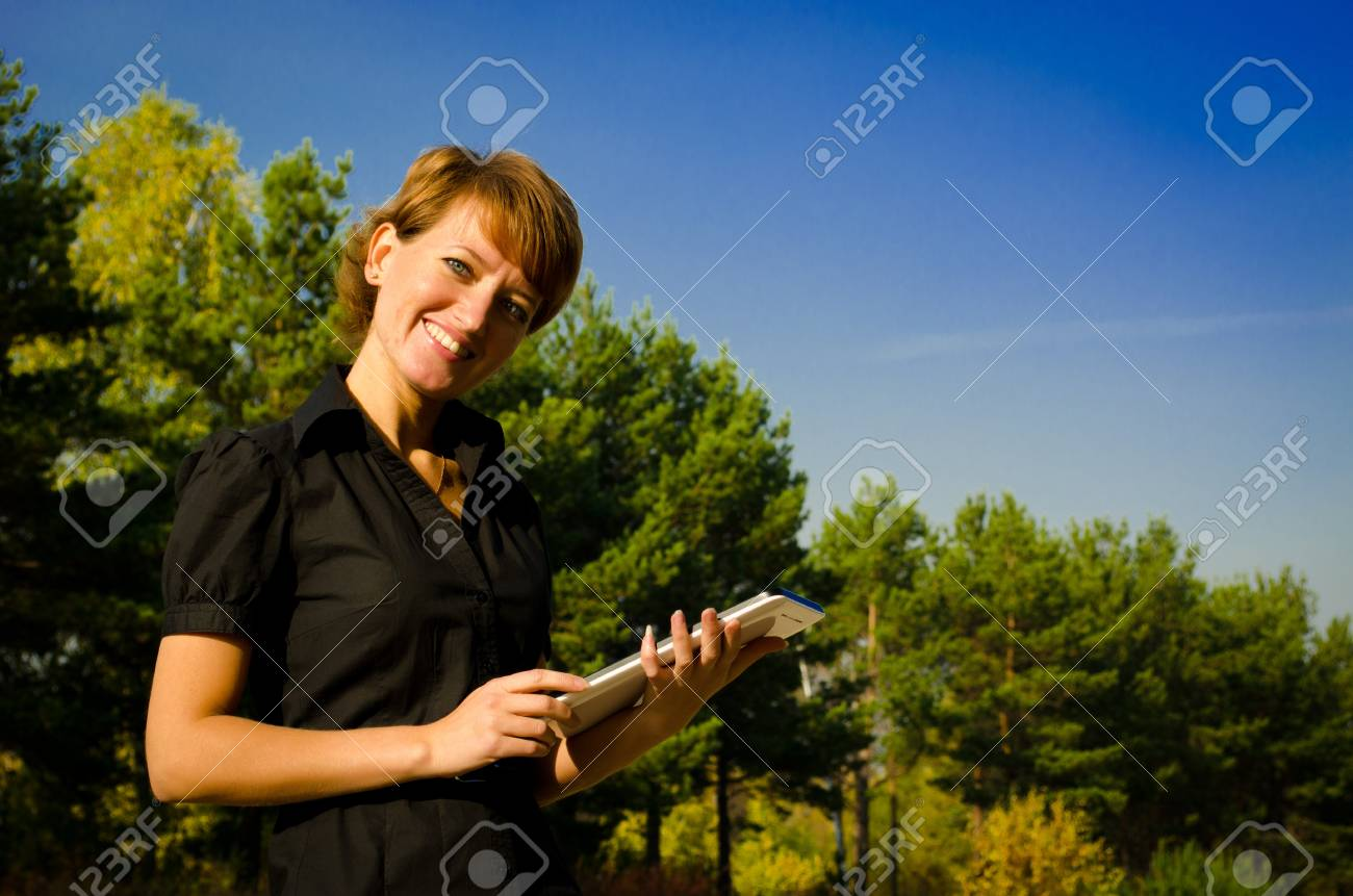 Young woman running on a Tablet PC in the autumn park Stock Photo - 15891629