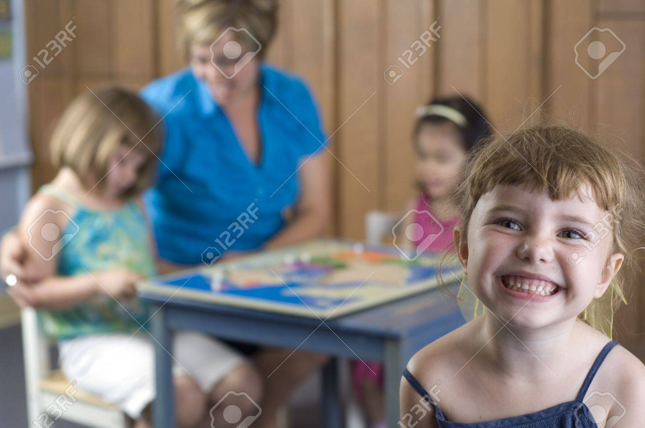 Children and teacher play and learn geography by using a puzzle map. Stock Photo - 7345903
