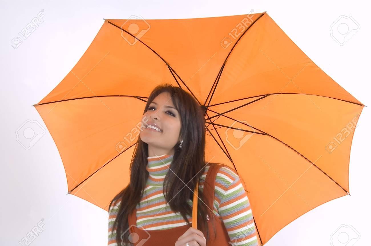 34611d84e49 Pretty girl with orange umbrella in her hand Stock Photo - 2570347