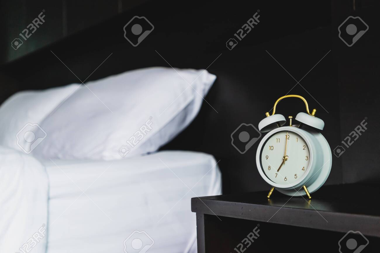 Retro gray alarm clock on the wooden bedside tables in the bedroom