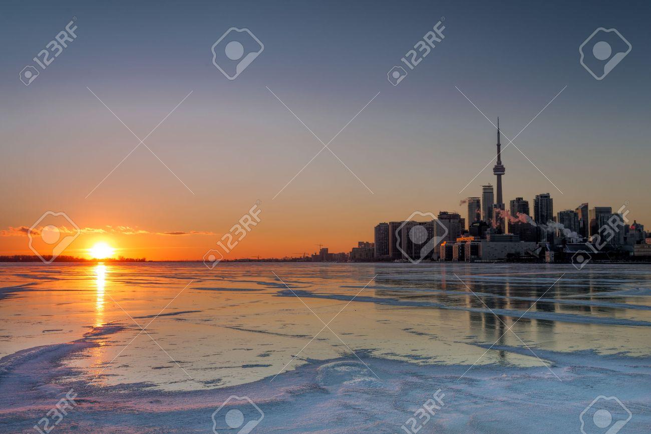 una puesta de sol de invierno magnfica sobre congelado lago ontario con el horizonte de