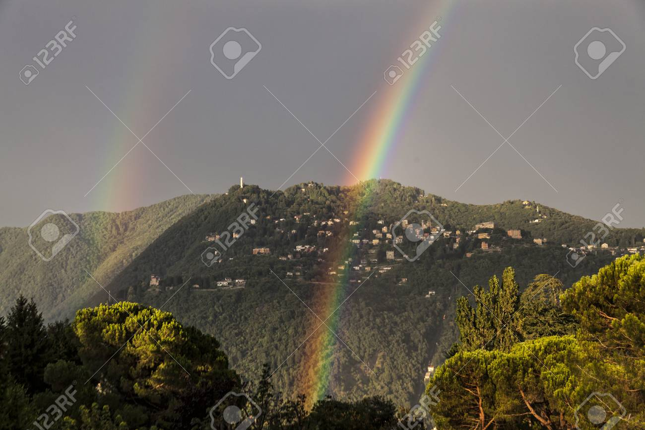 Double rainbow over the mountain overlooking Como. City of Brunate in summertime. Como Lake. Italy - 97244160