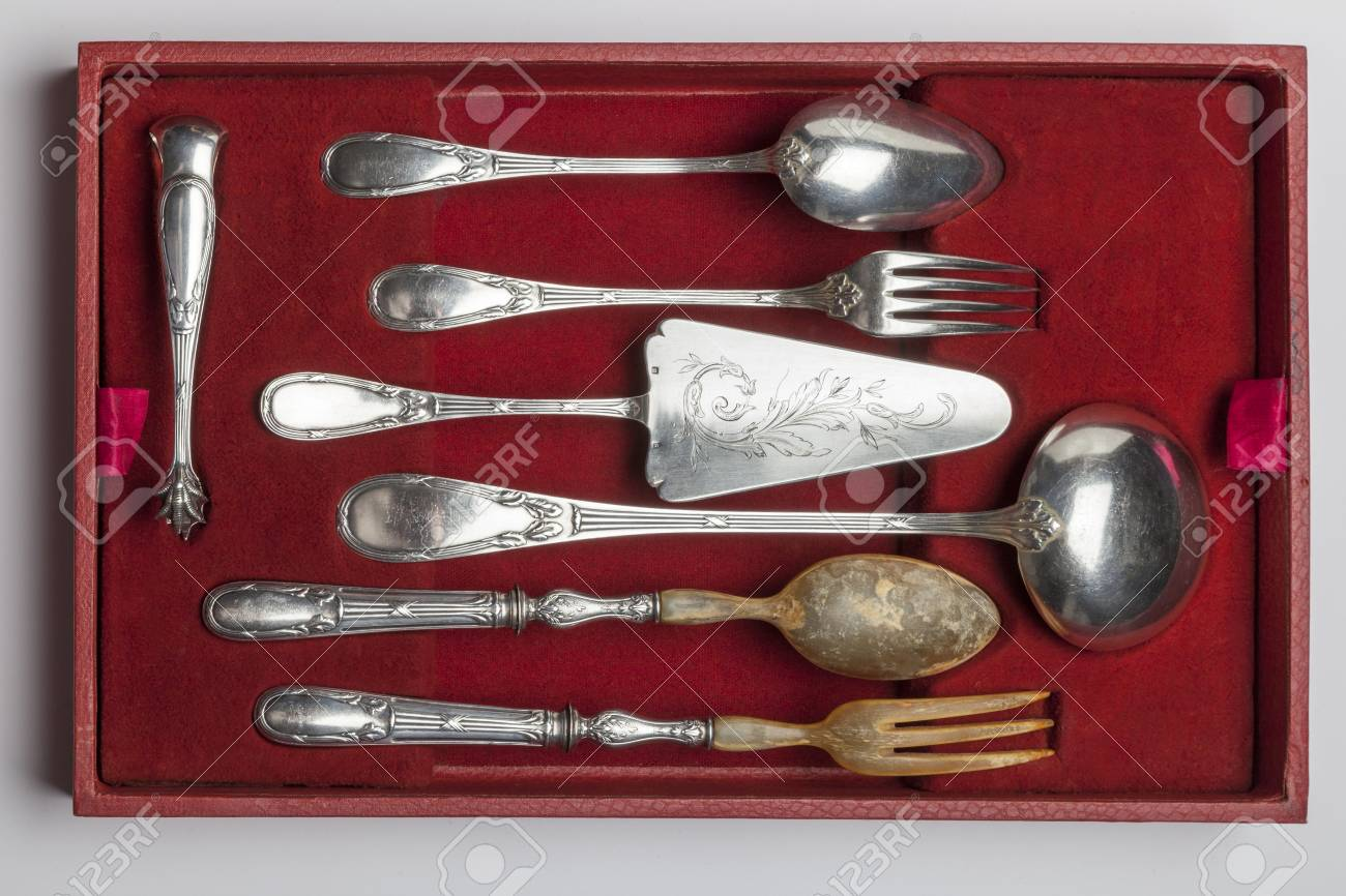Vintage silverware in red velvet box isolated on white background, circa 1920 - 97253799
