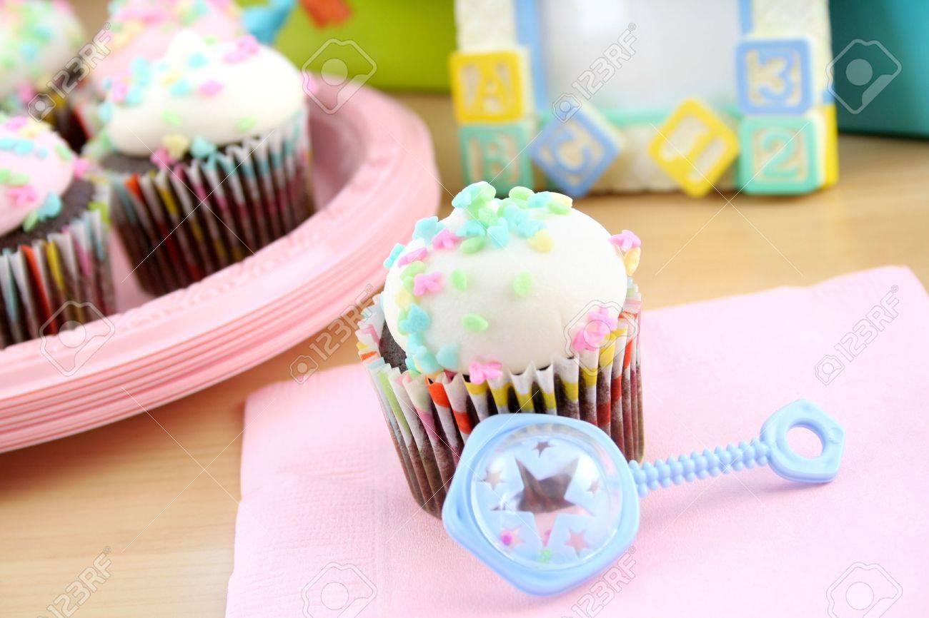 Cupcake Con Un Glaseado Blanco Y Pasteles Rocía Con Un Bebé Sonajero ...