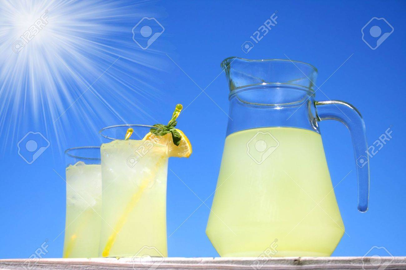 Glasses of lemonade outside with a bright blue sky and sun with sun rays. Stock Photo - 4970802