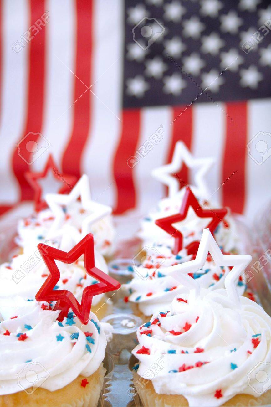 Cupcakes decorated in a patriotic theme with the American flag as a background.  Shot with a shallow depth of field and selective focus and room for text. Stock Photo - 4970804