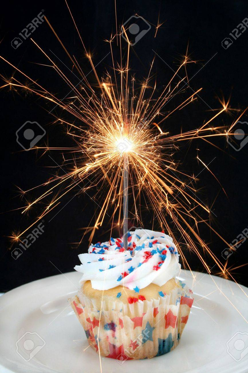 Fourth of July cupcake done with red and blue star shaped sprinkles and a sparkler firework as the candle. Stock Photo - 5058729
