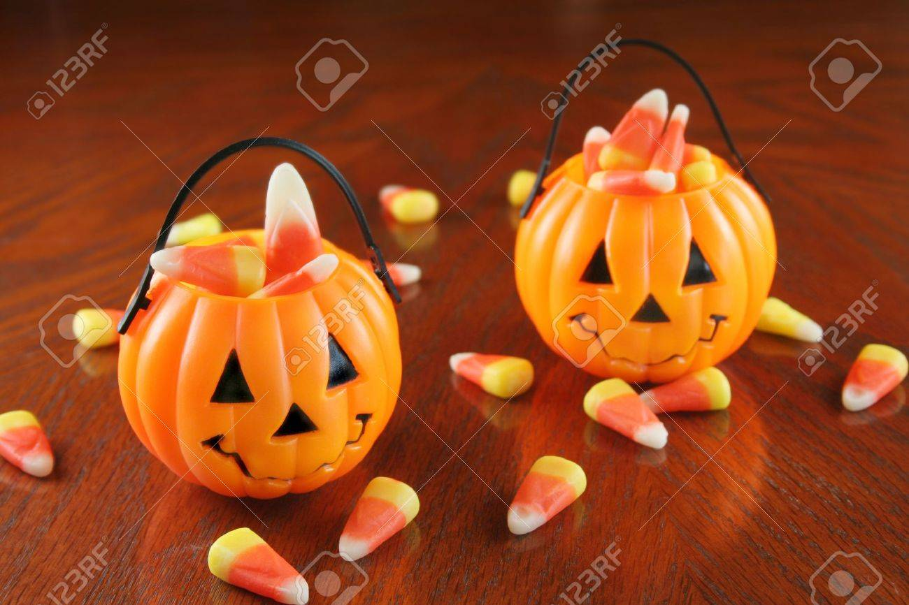 small plastic pumpkins holding candy corn with some laying on a table top stock photo - Plastic Pumpkins