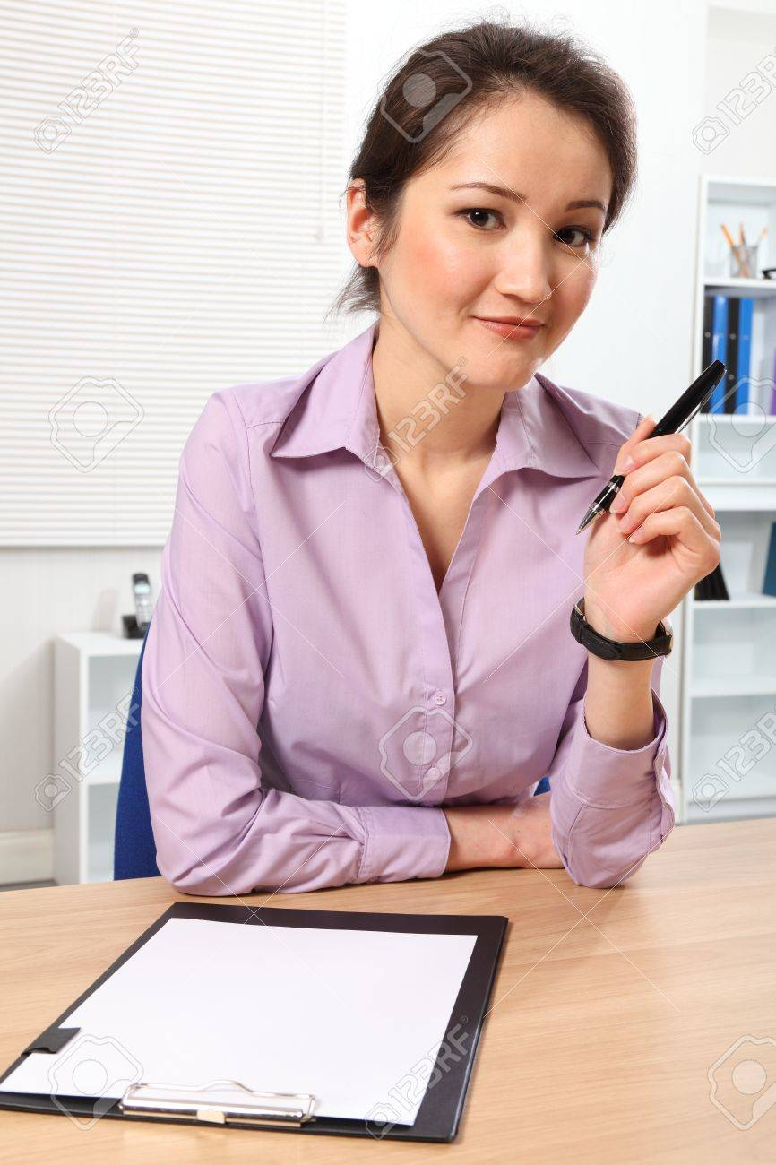 Woman sitting at desk with pen and clip board Stock Photo - 9567653