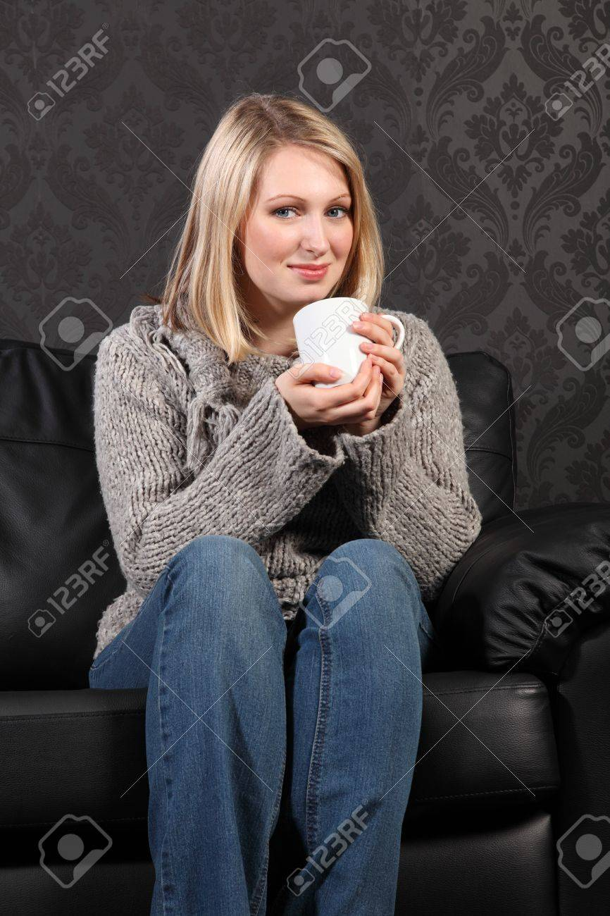 25aba867b0af4 Stock Photo - Thoughtful moment for beautiful young blonde woman sitting on  black leather sofa at home drinking coffee, wearing casual grey knitted  sweater, ...