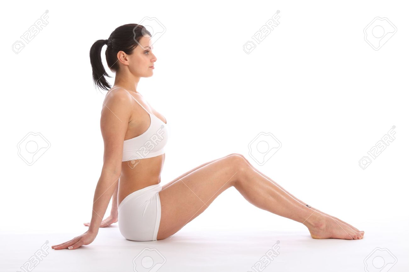 Profile view of beautiful healthy young woman wearing white sports underwear, sitting on floor with knees raised against white background showing off fit body and long legs. Stock Photo - 9746236