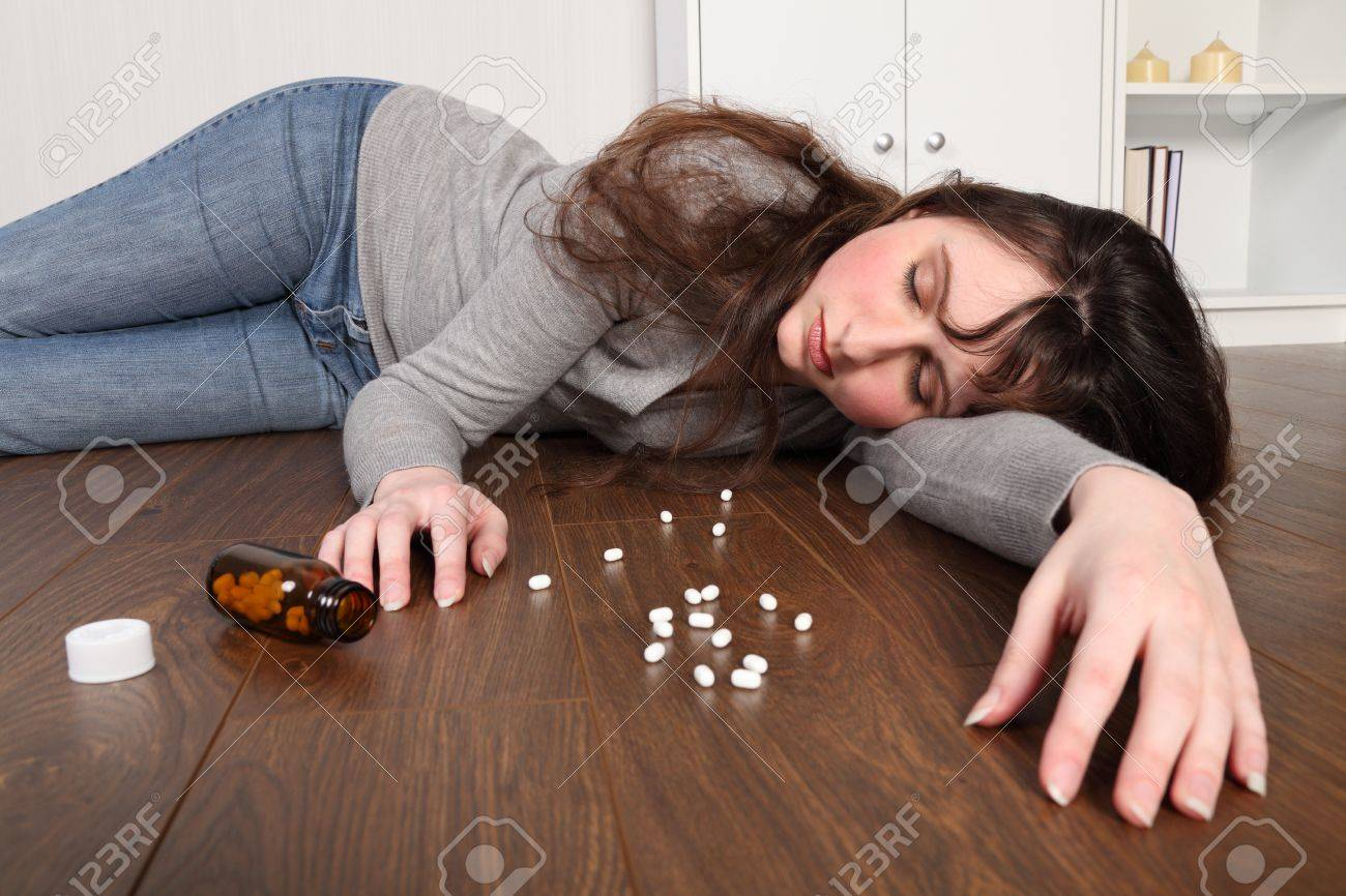 Young woman lying on the floor at home after an overdose of pills. Her eyes are closed and there is a bottle of pills on the floor beside her. Stock Photo - 9744984