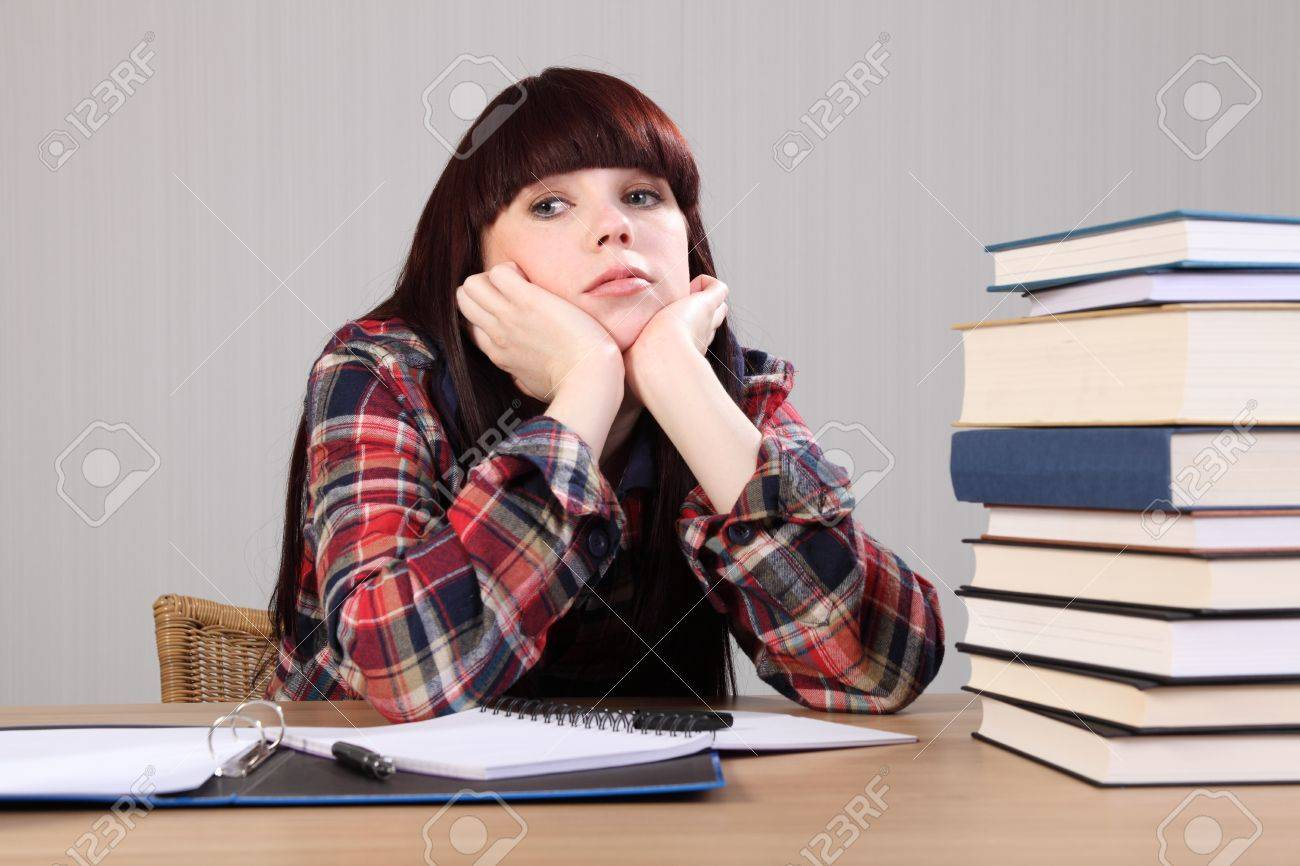 Young caucasian student girl at home, sitting to her desk with head resting on hands looking tired, taking a break from doing homework. Stock Photo - 9746721