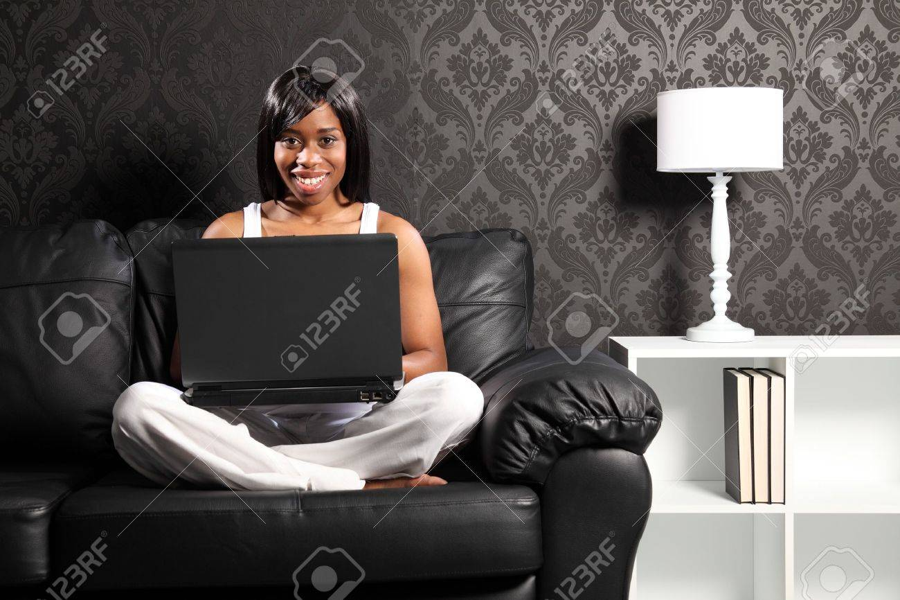 Beautiful smiling young black woman sitting cross legged on leather sofa at home, surfing the internet with her laptop computer. Stock Photo - 9747024