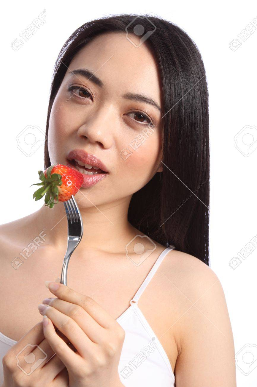 Close up of beautiful sexy young chinese girl, with long black hair, about to bite into a fresh strawberry fruit on a fork. Stock Photo - 9926252