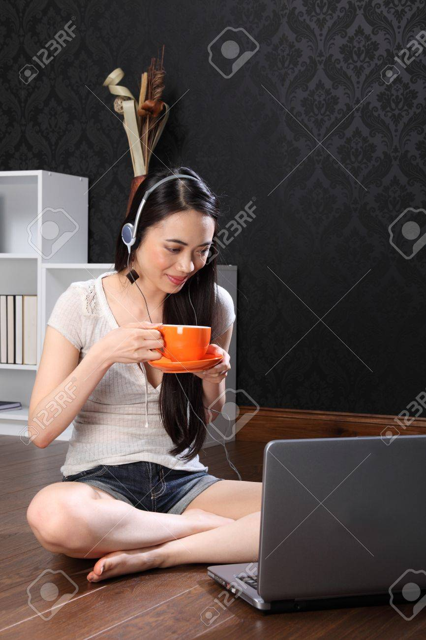 Smiling beautiful young oriental girl sitting on the floor at home drinking tea from an orange cup, wearing headphones while surfing the internet and facebook with her laptop computer. Stock Photo - 9926288