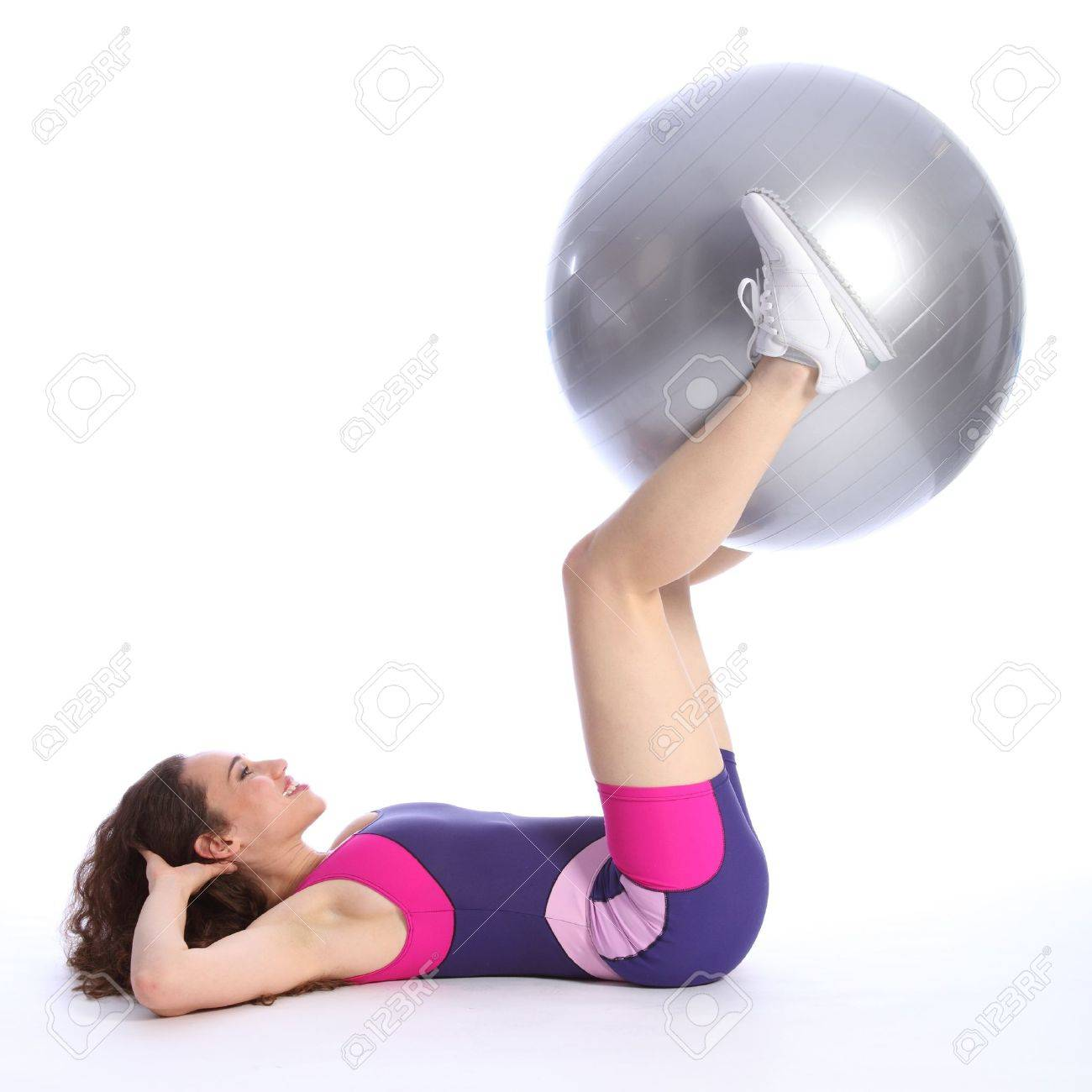 Fit beautiful brunette woman with big smile lying on the floor lifting exercise ball using her legs as part of workout routine. She is wearing bright blue and pink sports clothes and white trainers. Stock Photo - 9926572