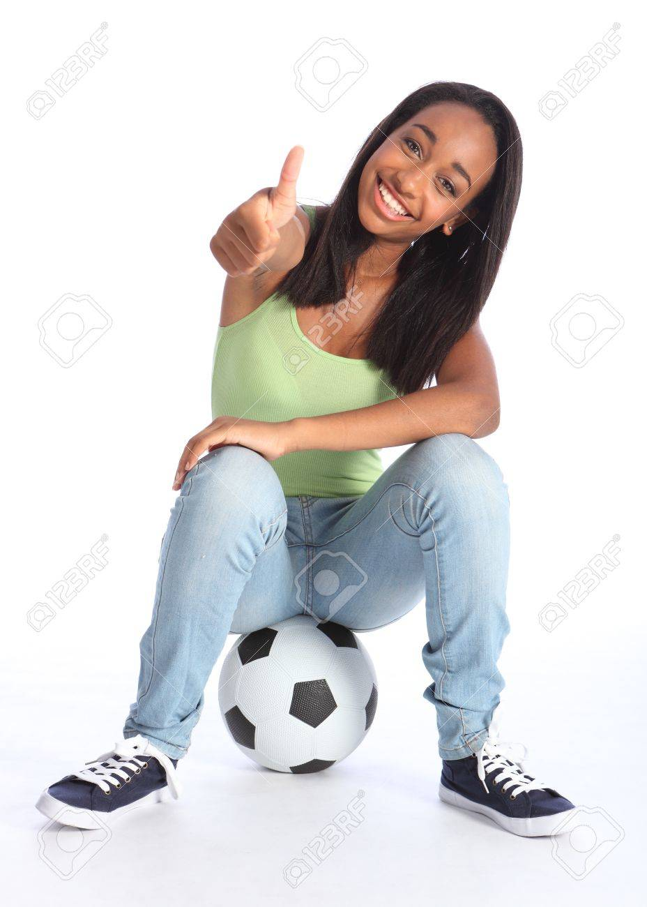 Football success for beautiful young African American teenage school girl soccer player, sitting on a ball with thumbs up sign. Girl wearing blue jeans and casual vest and has a big happy smile. Stock Photo - 10429853