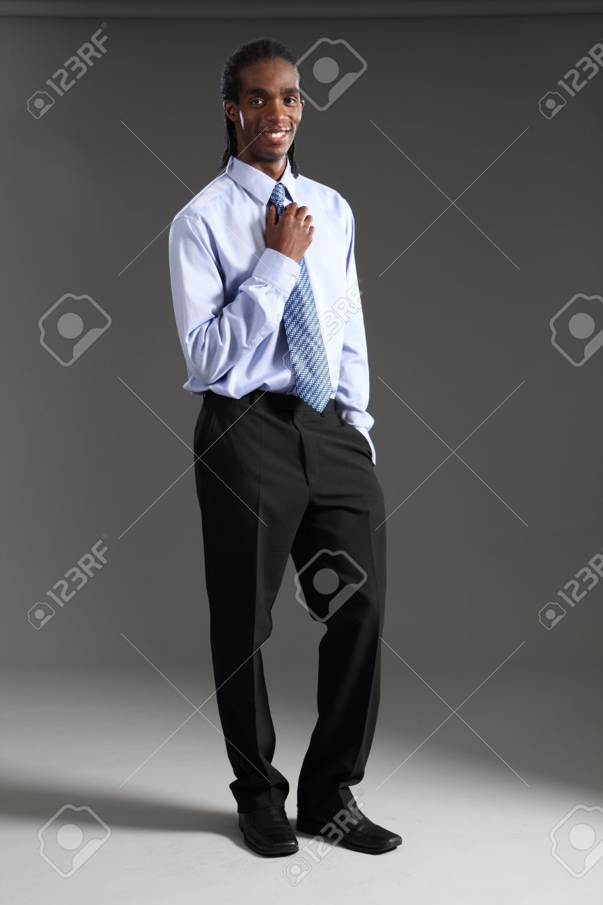 9a6d9ee81ba Handsome young African American businessman standing wearing black suit  trousers and blue shirt and neck tie