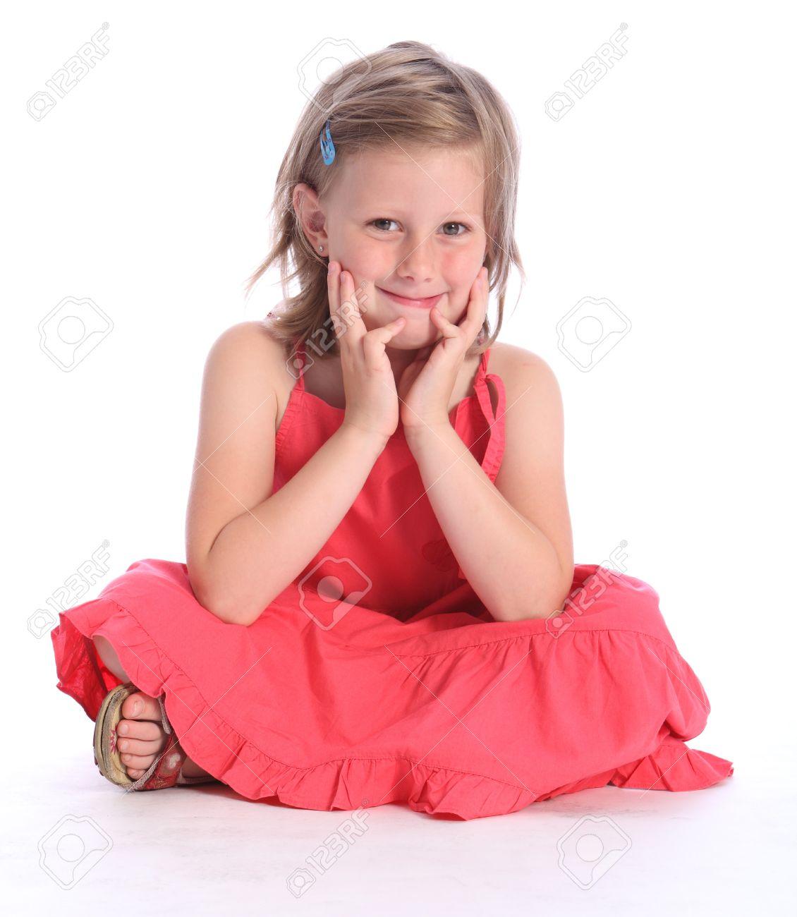 Linda Rubia De Seis Años Niña De La Escuela Primaria Con Un Vestido Rosa Coral Sentado Con Las Piernas Cruzadas En El Suelo Con Una Sonrisa Feliz
