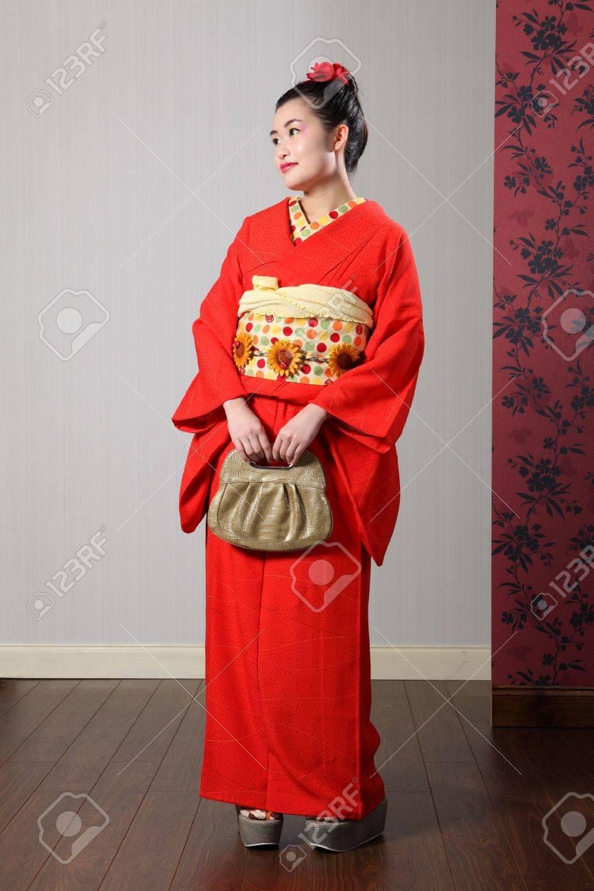 781c0b214ace Belle Jeune Femme Orientale En Portant Du Rouge Kimono Traditionnel Japonais,  Un Vêtement Pleine Longueur Robe Avec Ceinture Obi Et Tenant Un Sac à Main  ...