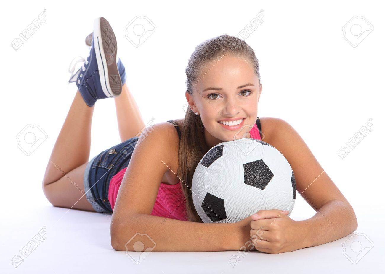 Fit young teenage athlete girl lying on the floor holding soccer ball with beautiful smile wearing pink vest and denim shorts. Full body shot against white background. Stock Photo - 10782755