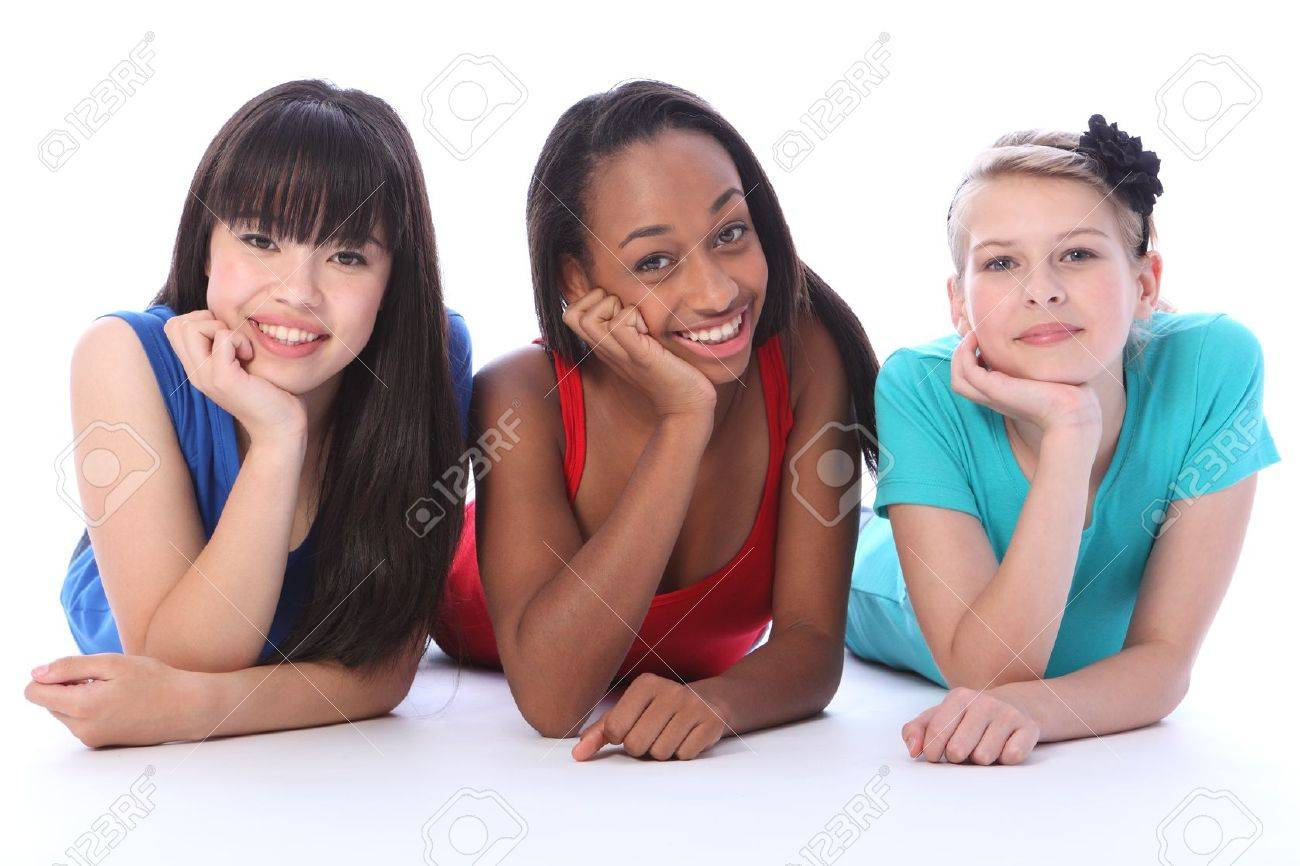 Teenage school student best friends lying on the floor together made up of mixed race african american, oriental Japanese and caucasian all with happy smiles having a laugh. Stock Photo - 10782761