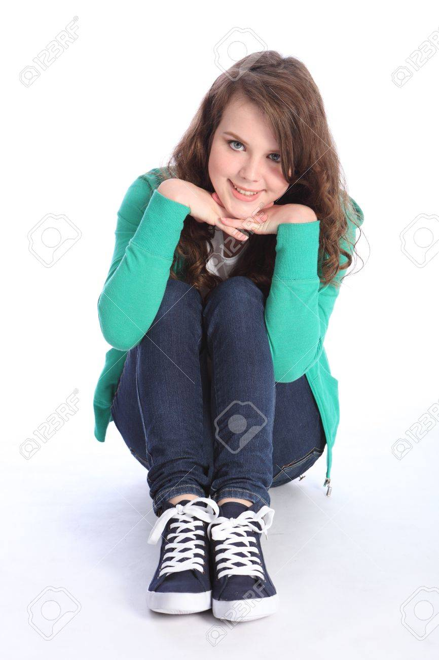 Beautiful blue eyes of a high school teenager girl with long brown hair wearing blue jeans and green jumper with big happy smile. Studio shot against white background. Stock Photo - 11296567