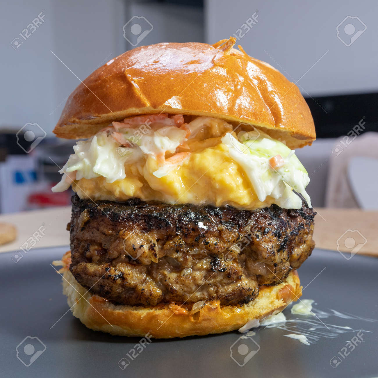 A big beef burger with scrambled eggs and coleslaw. - 156019545