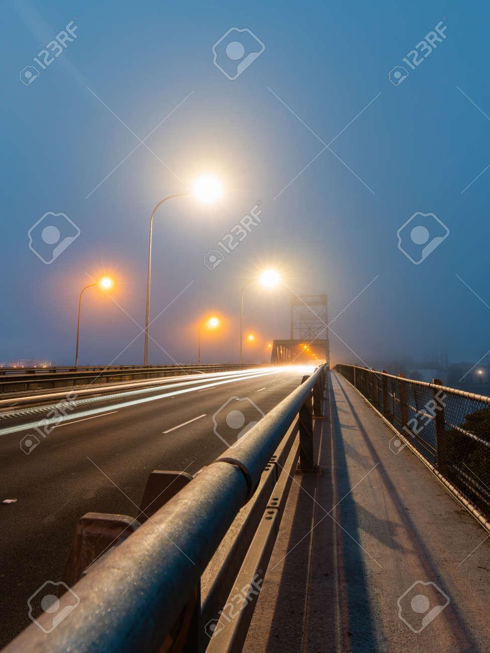 Car driving through fog at Ryde Bridge, Sydney, Australia. - 169167954