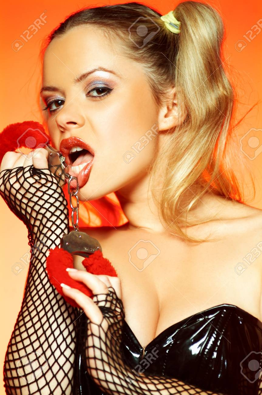 Portrait of beautiful young sexy woman on red background with handcuffs Stock Photo - 500342