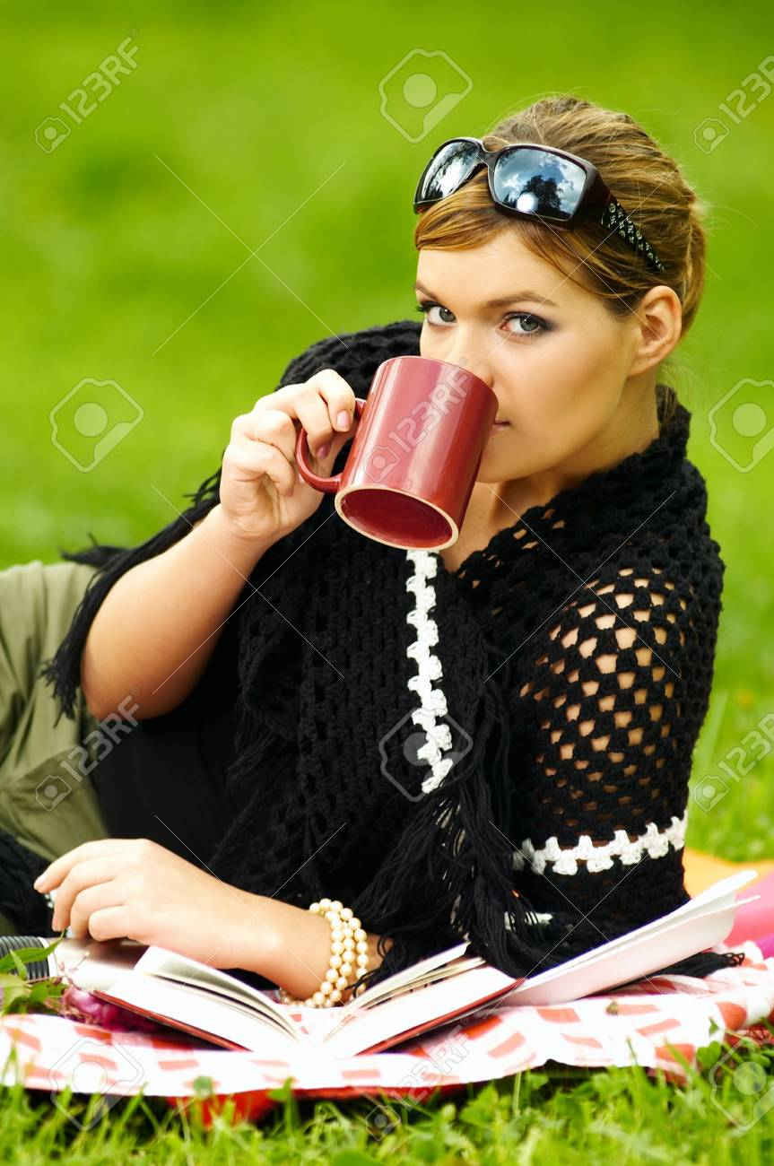 Young business woman with cup during picnic on green meadows outdoors Stock Photo - 550881
