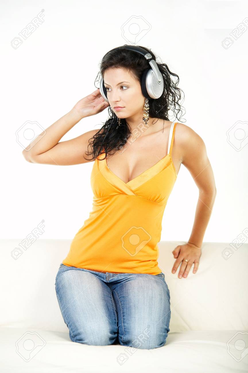Young beautiful happy women listening music in headphones on white couch Stock Photo - 561471