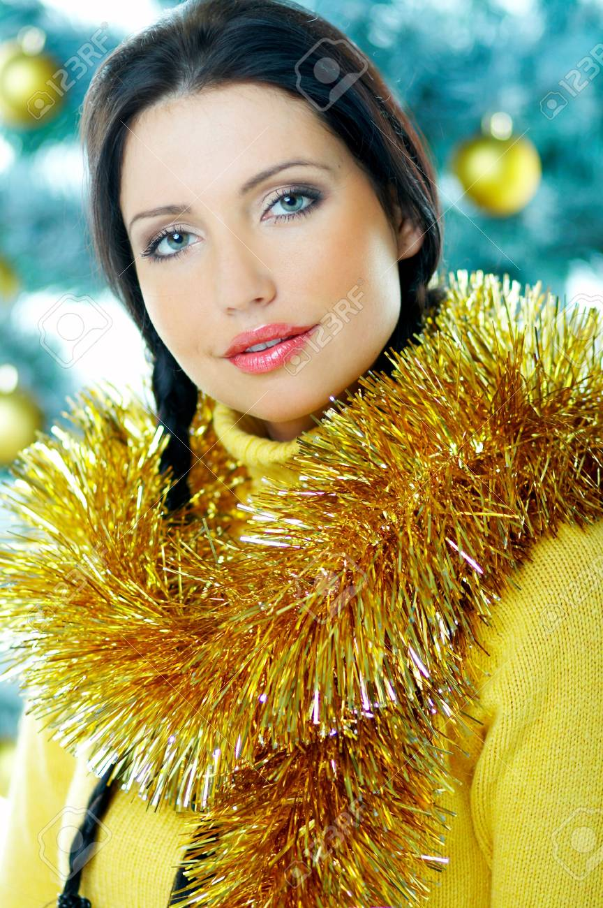 Beautiful brunette woman next to christmas tree with christmas chain on white background Stock Photo - 637347