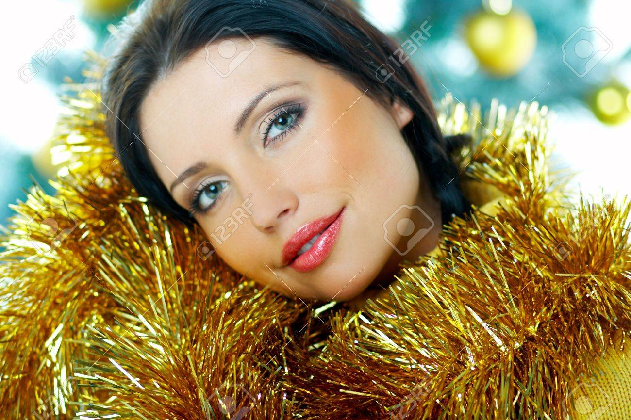 Beautiful brunette woman next to christmas tree with christmas chain on white background Stock Photo - 636992