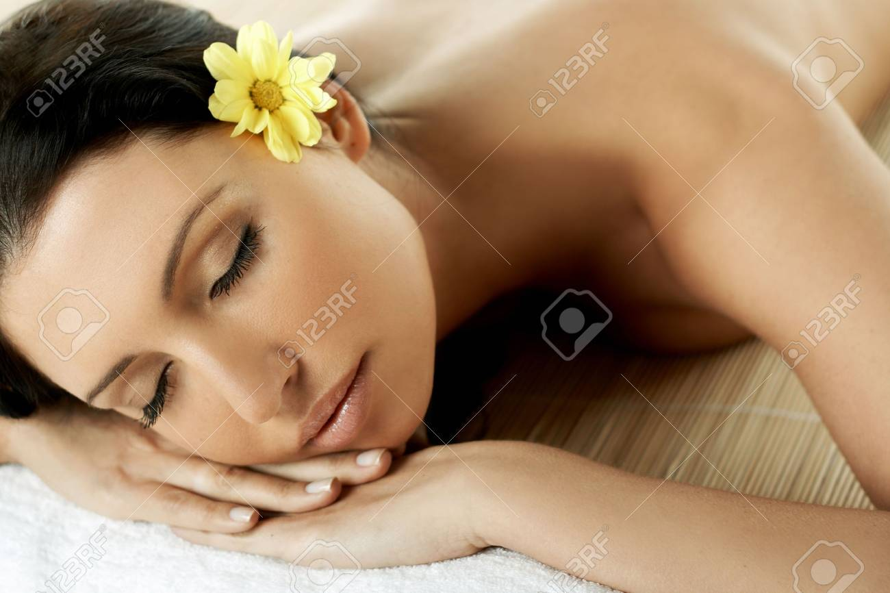 Portrait of Fresh and Beautiful brunette woman laying on bamboo mat around yellow flowers Stock Photo - 672533