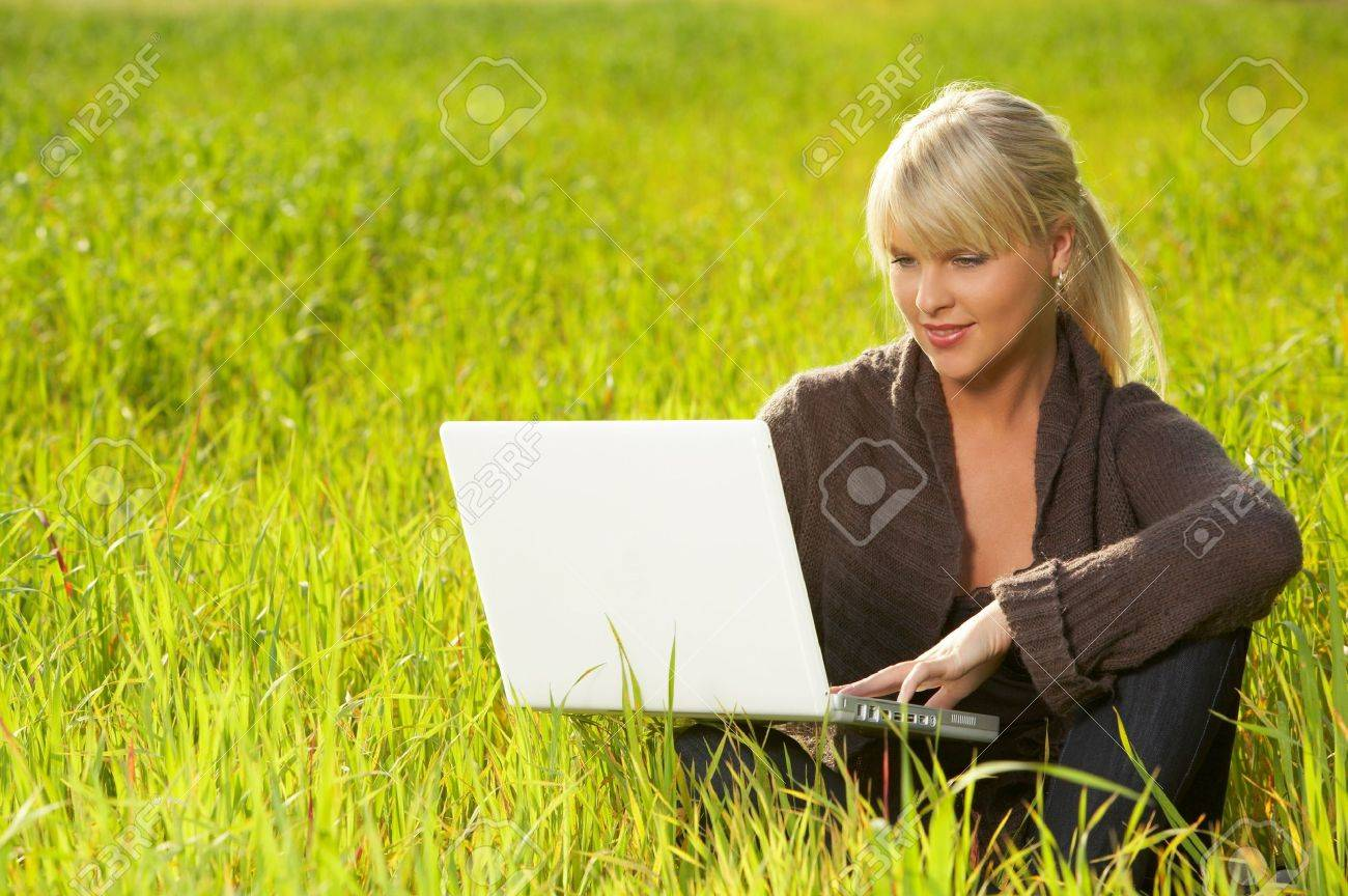 20-25 years old beautiful sexy woman portrait working on laptop computer on green grass meadow Stock Photo - 1789116