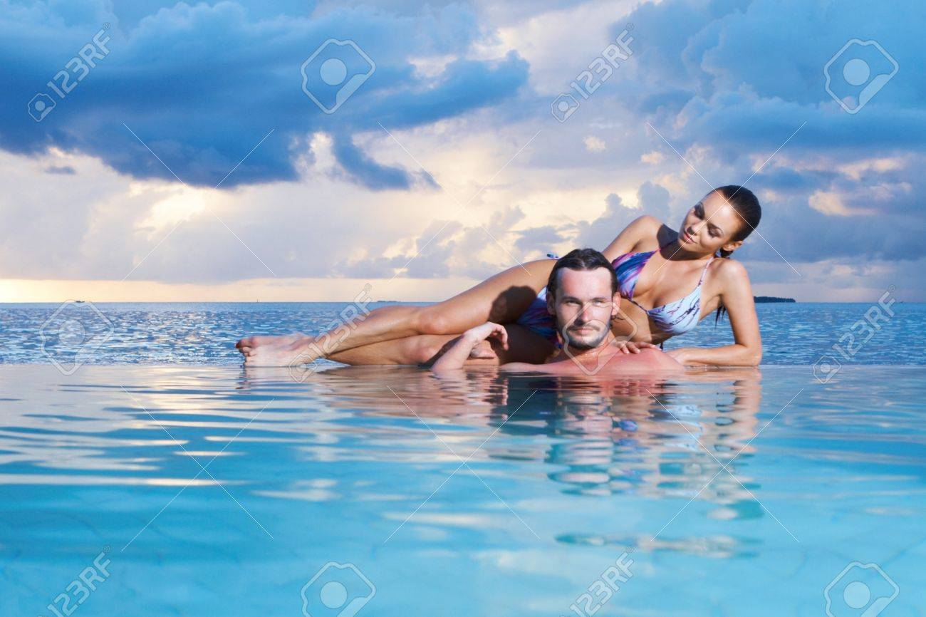 Romantic couple alone in infinity swimming pool Stock Photo - 7027182
