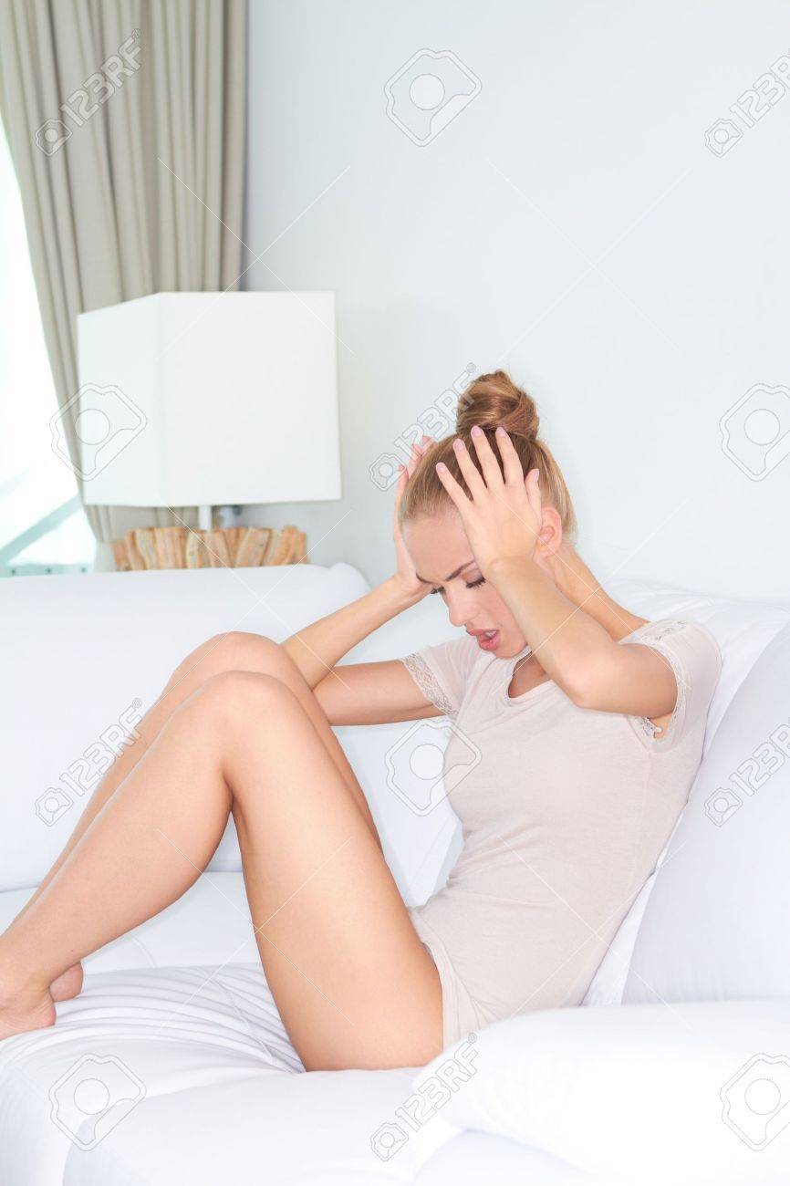 Beautiful woman sitting with her legs up on a sofa grimacing in pain from a migraine headache as she rubs her temples Stock Photo - 13201810