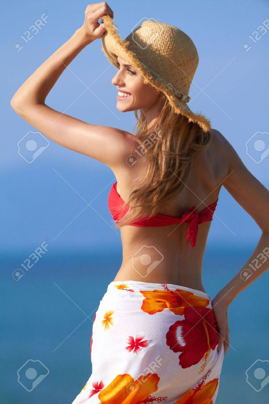Smiling blonde in a red bikini and sarong wrap with a hat for sun  protection Stock