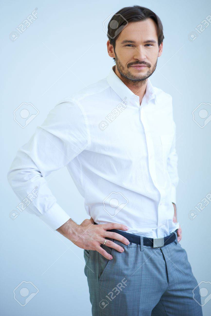 Good looking bearded young man standing looking at the camera with a smile with his hands on his hips Stock Photo - 17204053