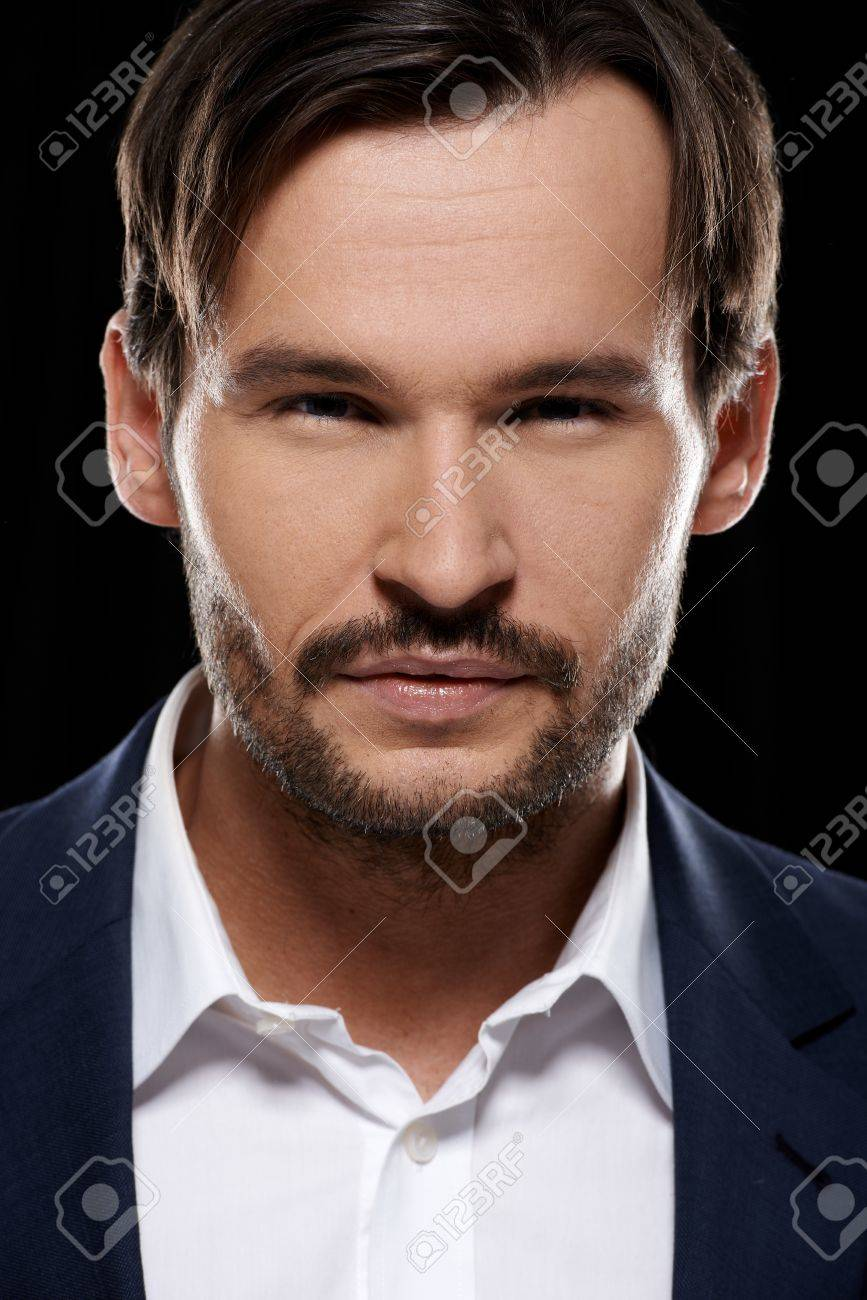 Cropped head portrait of a young handsome sexy bearded man on a dark studio background with deepset enigmatic eyes Stock Photo - 17204928