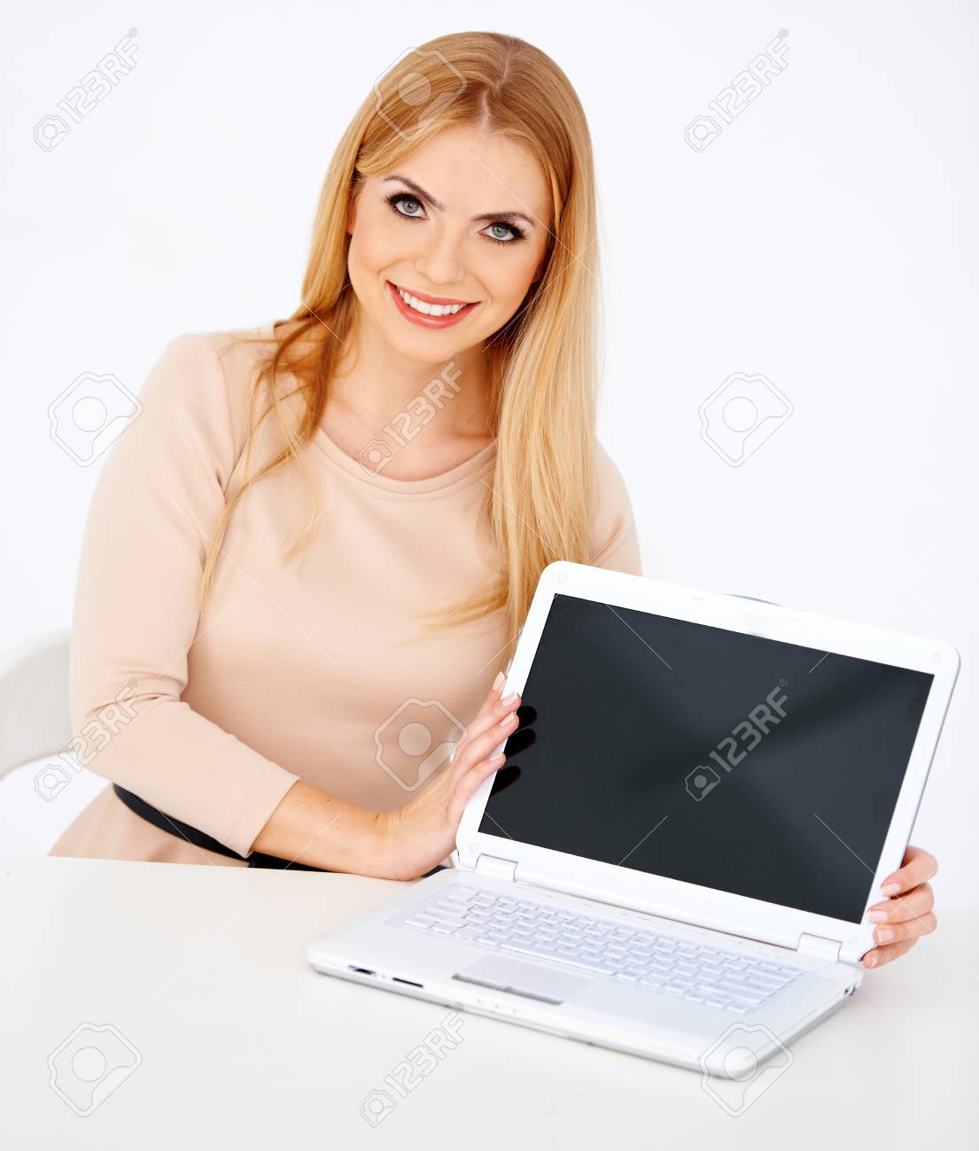 Pretty secretary sitting at desk and showing laptop Stock Photo - 17369653