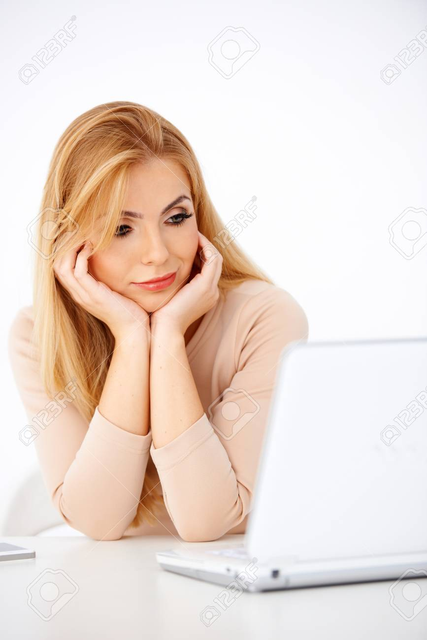 Attractive young blonde woman looking worried at her laptop Stock Photo - 17968820