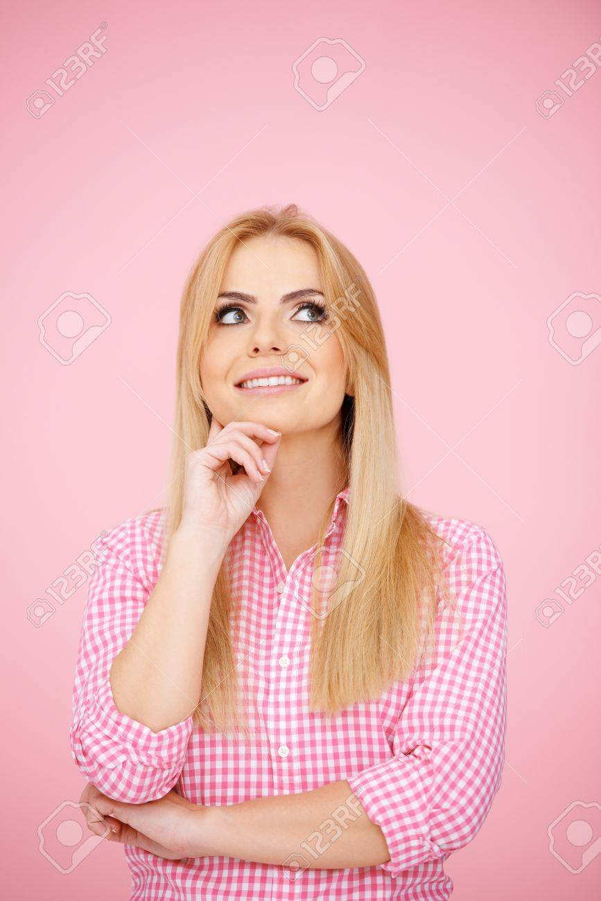 Thoughtful blond girl hatching an idea, on pink background Stock Photo - 17968919